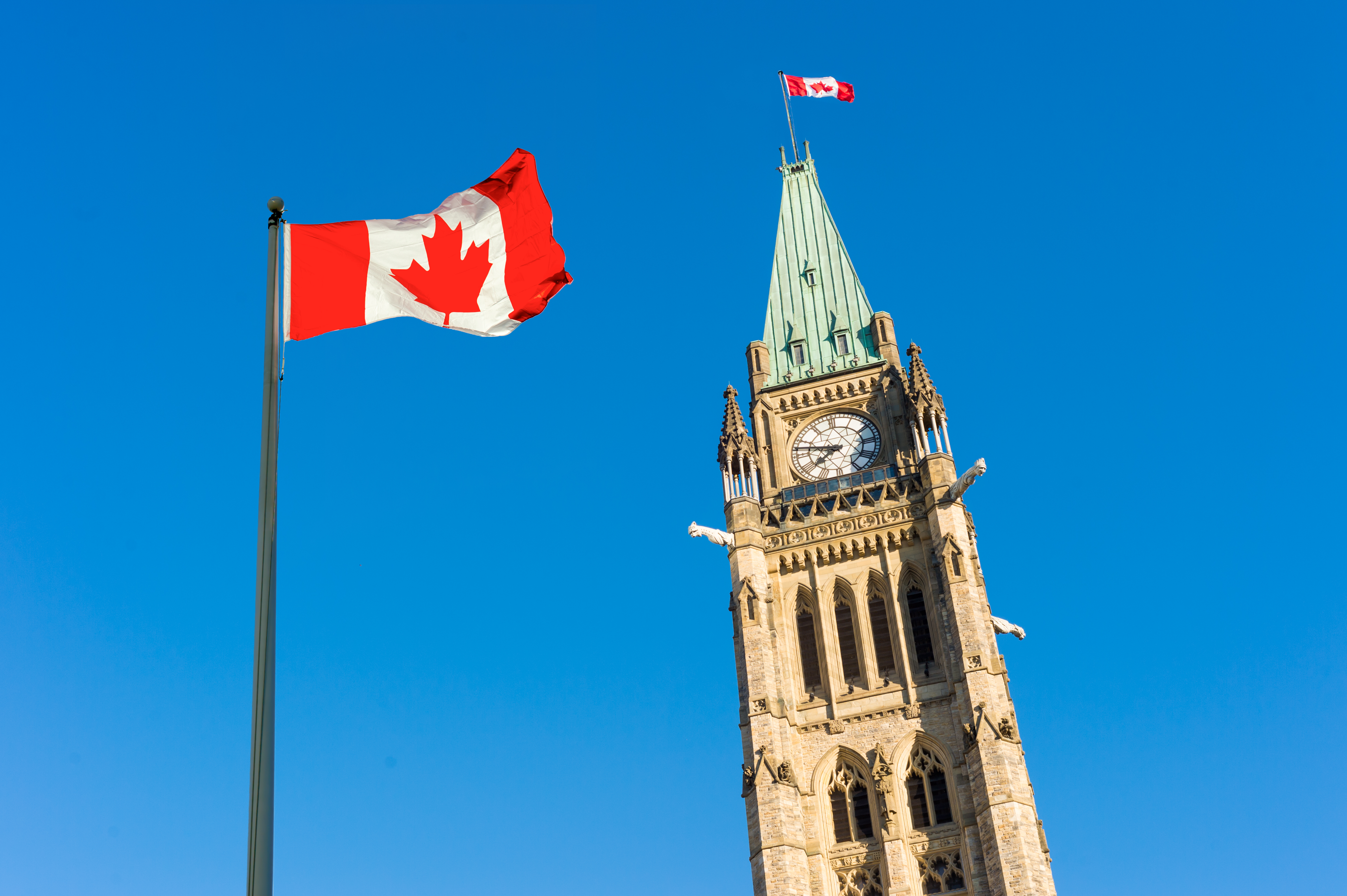 Close up of peace tower (parliament building)  with a big canadian flag over blue sky in Ottawa, Canada