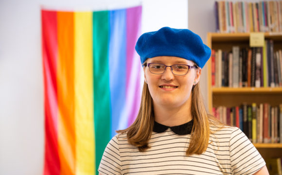 A photo of Penelope in a library standing in front of a rainbow flag wearing a blue beret.