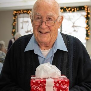 A photo of Bill holding a gift.