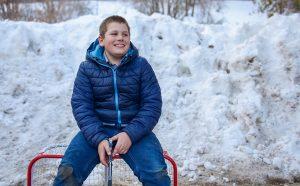 Boy sitting on top of mini hockey net, outside.