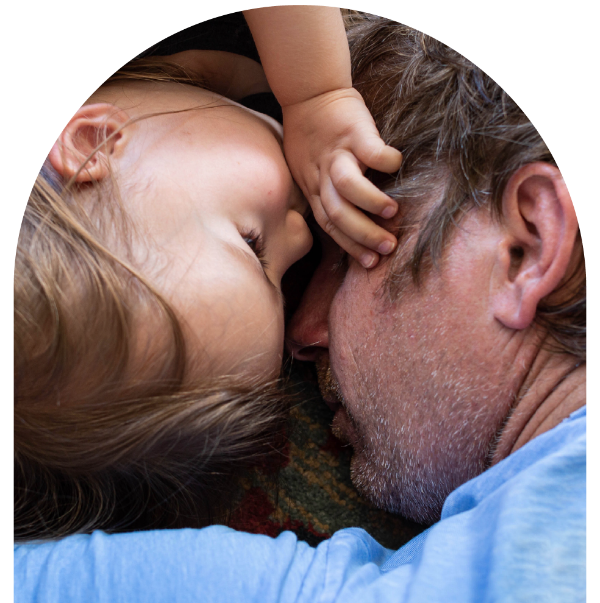 A father laying on the floor face to face with his daughter wishing for mental health supports.