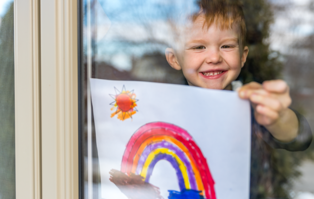 A kid holding up a painted rainbow in the window.