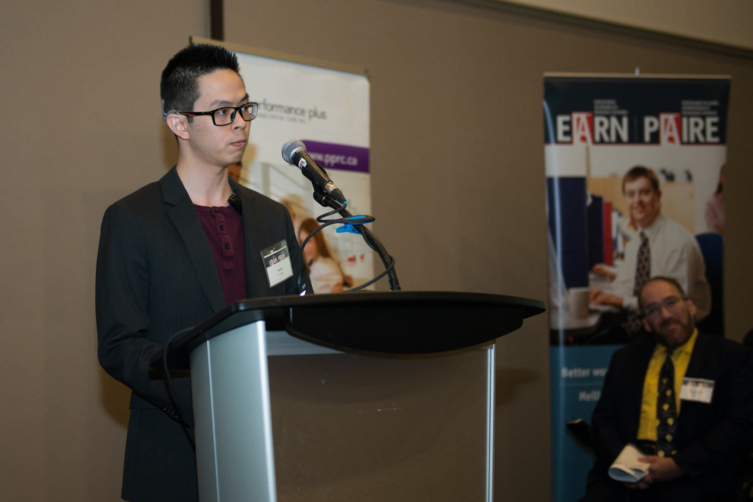 Yvan Le speaking at 2019 EARN conference podium