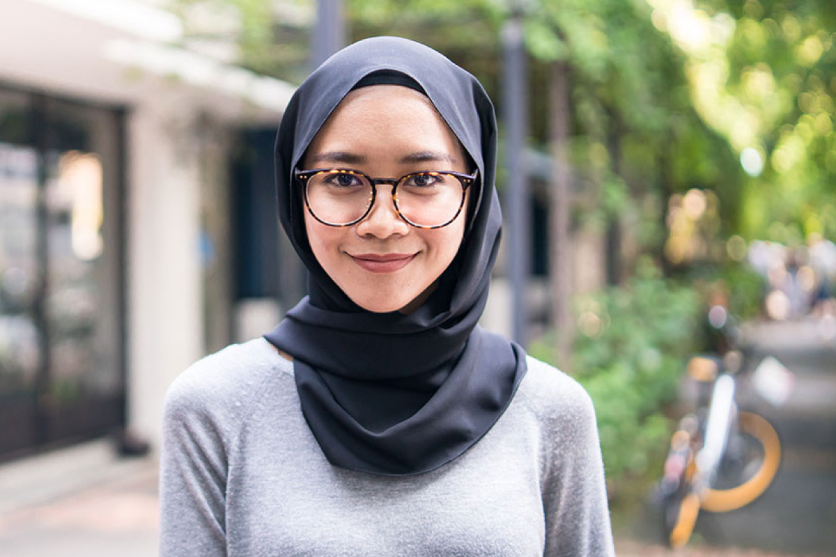 A photo of a woman wearing a hijab outside in the park.