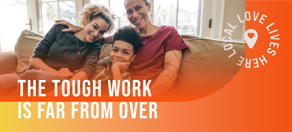 The Tough Work is Far From Over - A family sitting on the couch together smiling and laughing.
